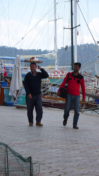 Bread-sellers with tray of fresh pretzels on his head, walking along Fethiye harbour