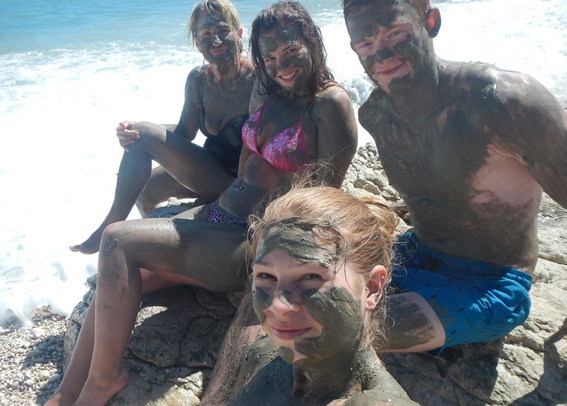 Four people sitting on rock covered in mud; softend the skin